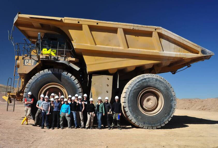 Students in front of a excavator